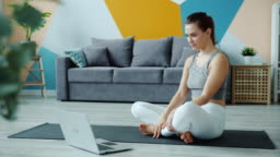Young woman doing yoga watching tutorial using laptop in apartment on mat