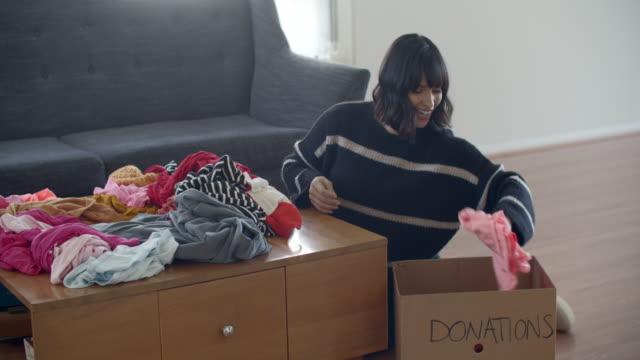 young woman donating used clothes - 再生利用点の映像素材/bロール