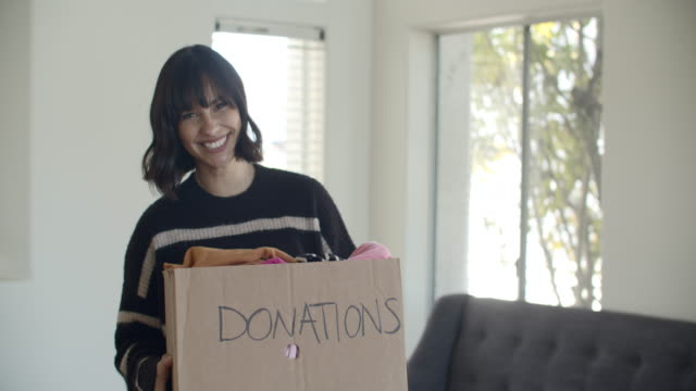 cu young woman donating used clothes - geben stock-videos und b-roll-filmmaterial