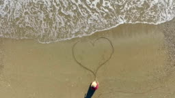 Young woman drawing heart on beach