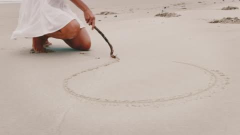 junge frau zeichnung herzform auf sand am strand - blondes haar stock-videos und b-roll-filmmaterial