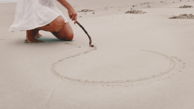 young woman drawing heart shape on sand at beach - caucasian ethnicity stock videos & royalty-free footage