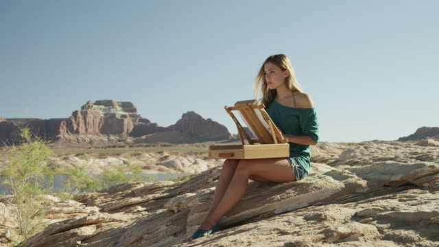 ws ds young woman drawing in desert landscape / lake powell, utah, usa - furzen stock-videos und b-roll-filmmaterial