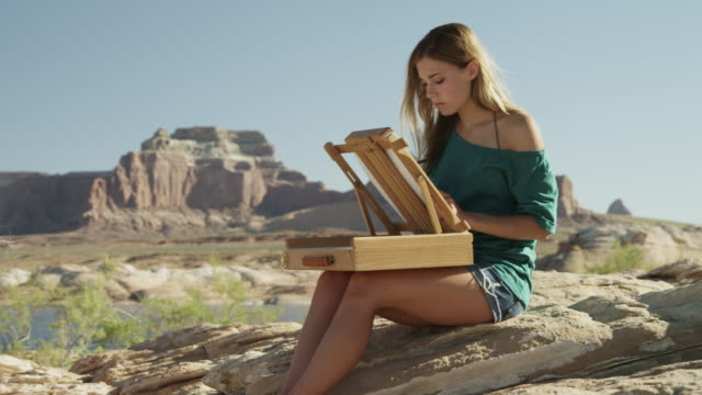 ws ds young woman drawing in desert landscape / lake powell, utah, usa - lake powell stock videos & royalty-free footage