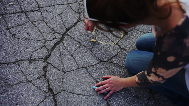 young woman drawing smiley face with chalk on asphalt - gekritzel zeichnung stock-videos und b-roll-filmmaterial