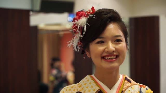 A young woman dressed in a furisode style kimono prepare for a Coming of Age Day ceremony at a photo studio in Kawasaki City Kanagawa Prefecture...