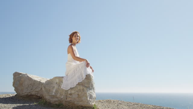 young woman dressed in white sitting on rock and looking out to sea