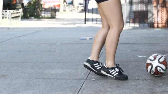 A young woman dribbles a soccer ball in the streets of New York - closeup - slow motion - 4k