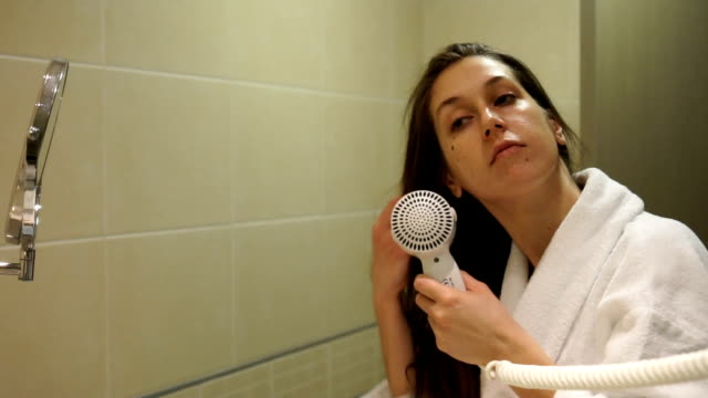 young woman dries wet hair in front of mirror with hairdryer - slow mo - wet hair stock videos & royalty-free footage