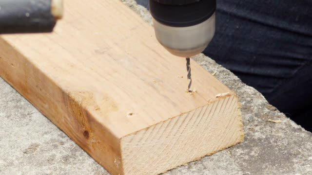 A young woman drills holes into wood for nailing in slow motion.