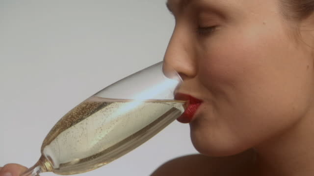 vidéos et rushes de slo mo, ecu, young woman drinking champagne in studio, portrait - champagne