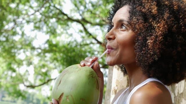 vídeos de stock, filmes e b-roll de água bebendo do coco da mulher nova no parque - viagem