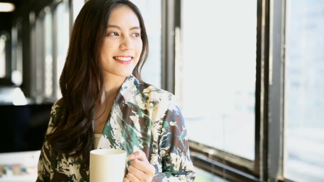 young woman drinking coffee and looking out the window with relax and happy - coffee break stock videos & royalty-free footage