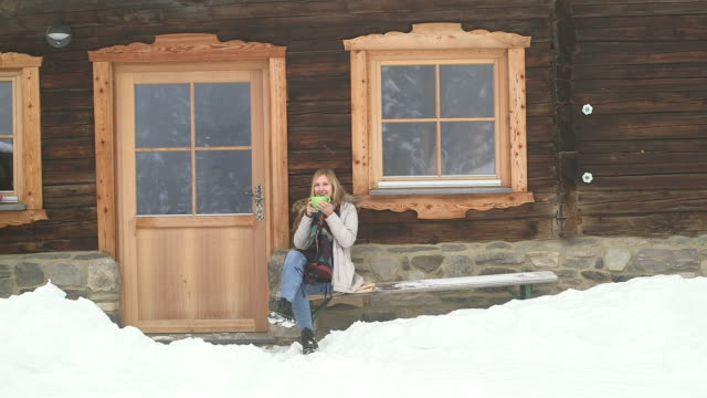 young woman drinking coffee and smiling - chalet video stock e b–roll