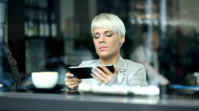 young woman drinking coffee and using tablet - hoozone stock videos and b-roll footage