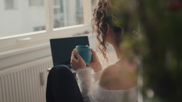 young woman drinking coffee at home smiling - coffee cup stock videos & royalty-free footage