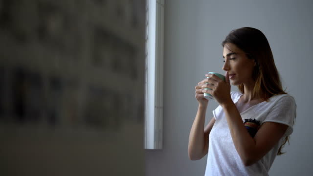 young woman drinking coffee at home - braunes haar stock-videos und b-roll-filmmaterial
