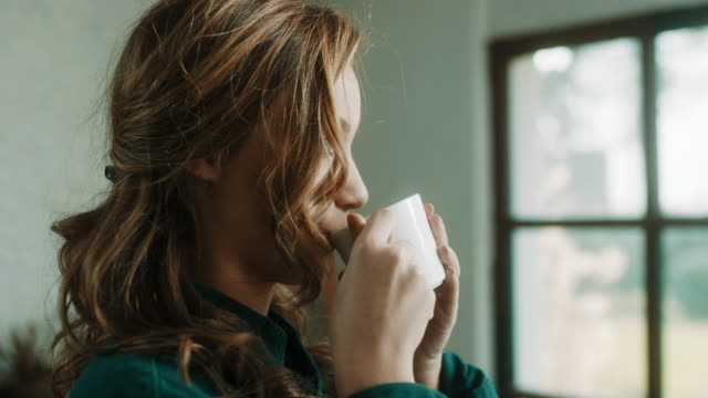 young woman drinking coffee in front of the window at artistic atelier - mug stock videos & royalty-free footage