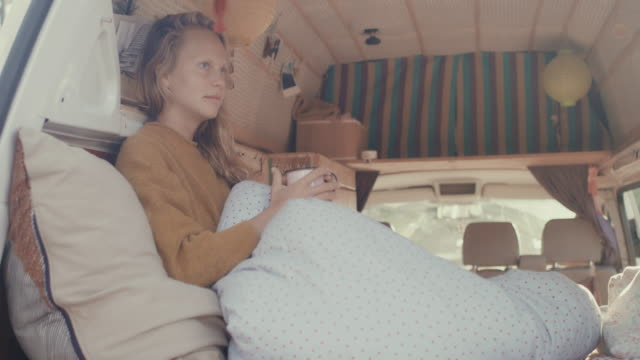 Young woman drinking coffee in the back of her motor home with cozy interior.