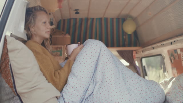 young woman drinking coffee in the back of her motor home with cozy interior. - generation z stock-videos und b-roll-filmmaterial
