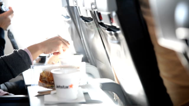 Young woman drinking coffee on an airplane , slow motion
