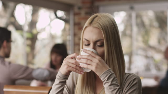Ung kvinna dricker kaffe