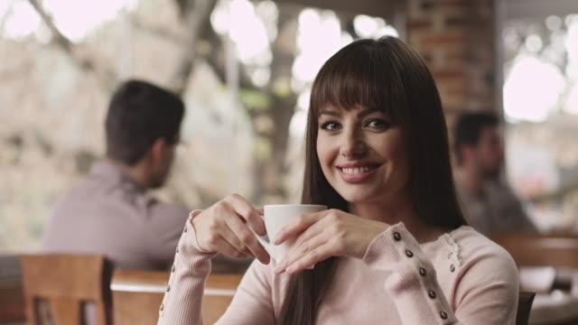 junge frau trinkt kaffee - tasse oder becher stock-videos und b-roll-filmmaterial