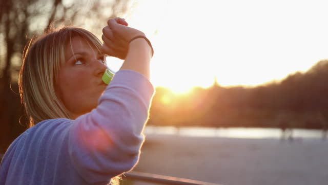 Young woman drinking from water bottle during jog