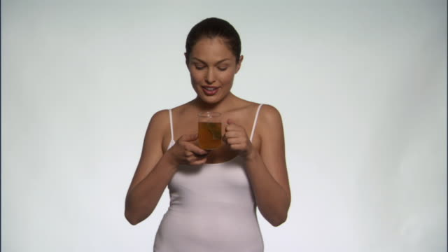slo mo, ms, young woman drinking herbal tea in studio, portrait - see other clips from this shoot 125 stock videos and b-roll footage