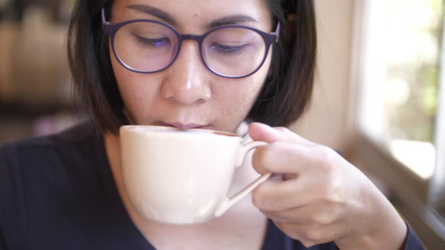 slo mo young woman drinking hot chocolate - heat stock videos & royalty-free footage
