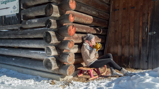 Young woman drinking hot tea in front of a log cabin in winter