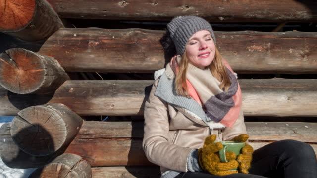 vídeos y material grabado en eventos de stock de young woman drinking hot tea in front of a log cabin in winter - cabaña de madera