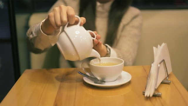 young woman drinking hot tea in the teahouse. - chinese tea cup stock videos and b-roll footage