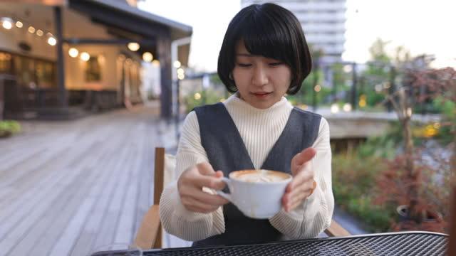 vidéos et rushes de jeune femme buvant le latte au café extérieur - patio