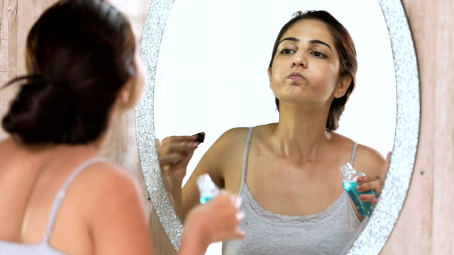 young woman drinking mouth wash in bathroom, delhi, india - domestic bathroom stock videos & royalty-free footage