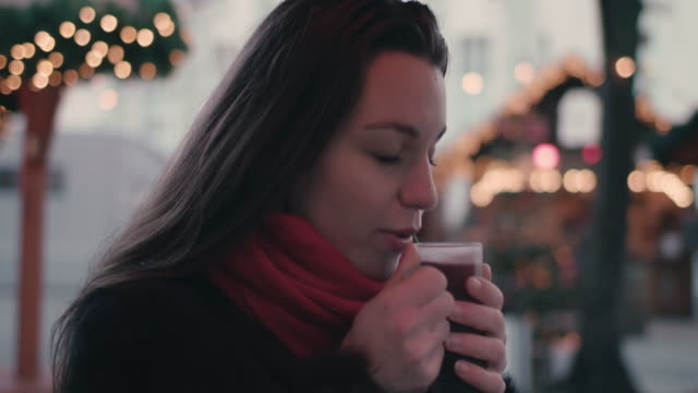 vidéos et rushes de young woman drinking mulled wine at christmas market - boisson chaude