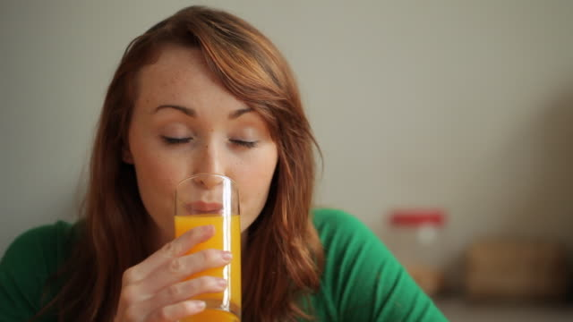 cu young woman drinking orange juice and smiling - orangensaft stock-videos und b-roll-filmmaterial