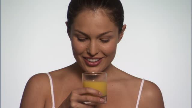 SLO MO, CU, Young woman drinking orange juice in studio, portrait