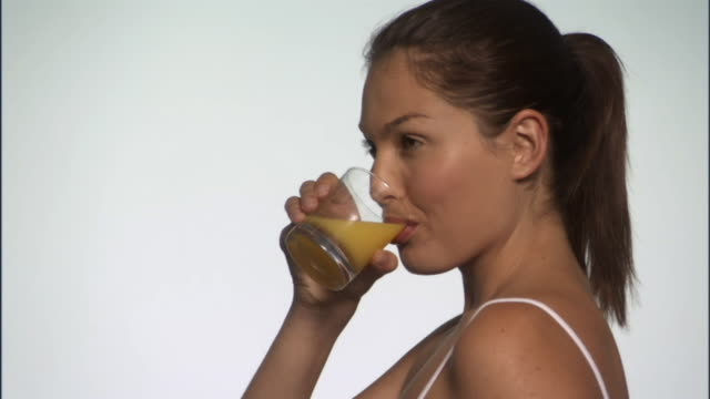 vídeos y material grabado en eventos de stock de slo mo, cu, young woman drinking orange juice in studio, portrait, tu - zumo de naranja