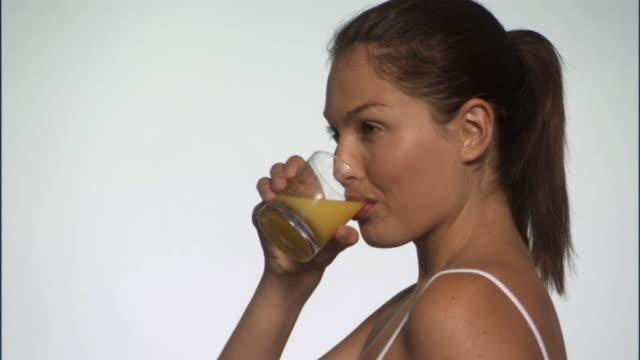 SLO MO, CU, Young woman drinking orange juice in studio, portrait, TU