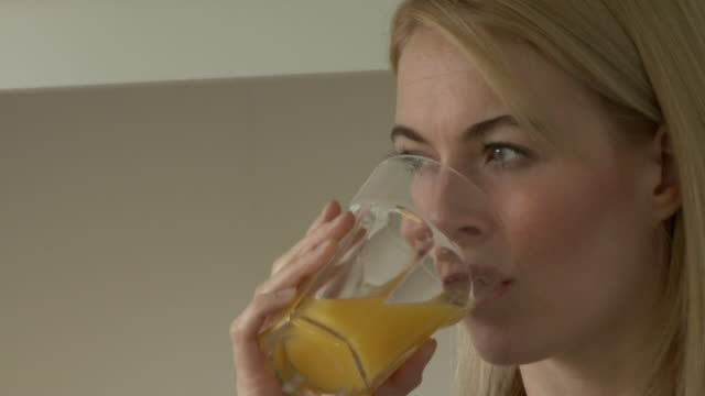 young woman drinking orange juice; uk - holding stock videos & royalty-free footage
