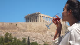 Young woman drinking red glass on home balcony with view on Parthenon, Acropolis of Athens, Greece. Fashion elegant white dress.