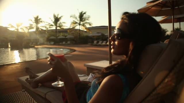 vidéos et rushes de young woman drinking red wine in a resort  - rebord de piscine