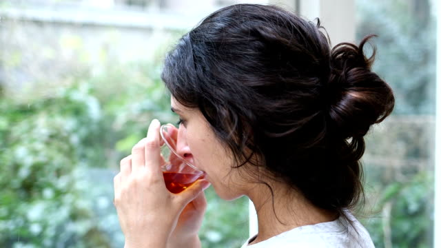 Young woman drinking tea and looking to camera
