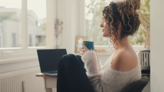 young woman drinking tea at home in front of laptop - resting stock videos & royalty-free footage
