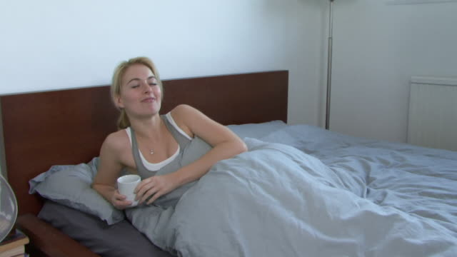 Young woman drinking tea in bed, UK