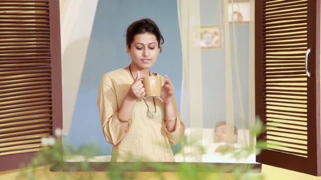 young woman drinking tea near window, delhi, india - indian couple tea stock videos & royalty-free footage
