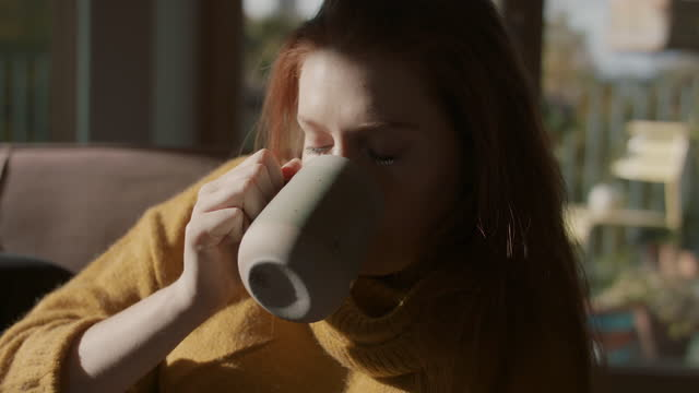 young woman drinking tea on sofa at home - sofa stock videos & royalty-free footage