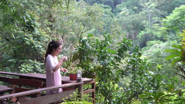 stockvideo's en b-roll-footage met jonge vrouw die thee of koffie drinkt in de bergen in een berg - enkel object