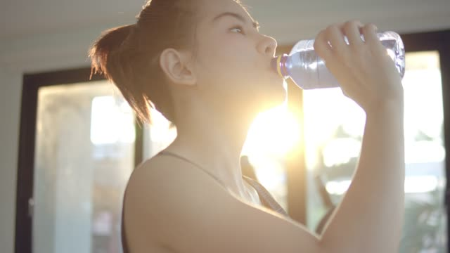 young woman drinking water after exercising - exercise machine stock videos & royalty-free footage